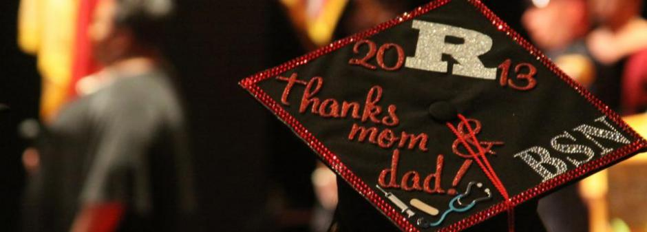 Photograph from above and behind a graduate of graduate's mortarboard. Mortarboard is black and decorated with red and silver writing. It reads: 2013. Thanks mom and dad. BSN.