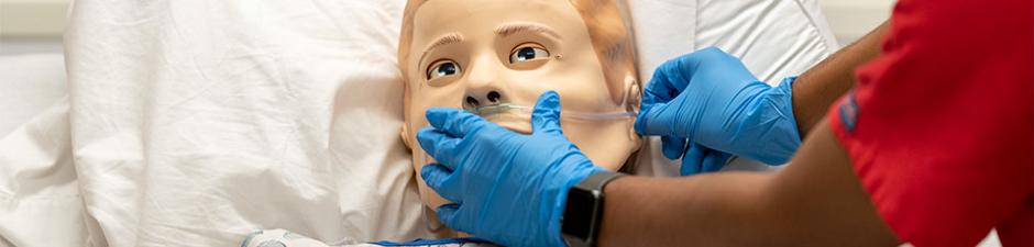 ABSN student applies oxygen mask to simulation mannequin